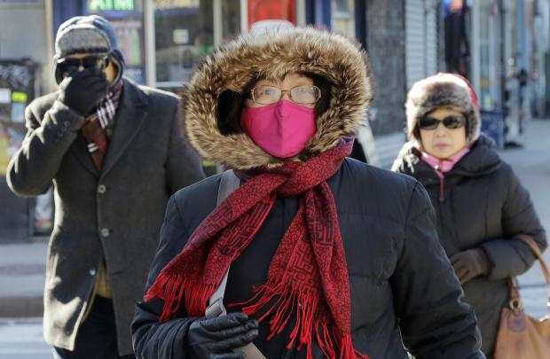 People are bundled up as they walk in cold weather, Sunday, Feb. 14, 2016, in the Queens borough of New York. Bitter temperatures and biting winds had much of the northeastern United States bundling up this weekend. (AP Photo/Mark Lennihan) ORG XMIT: NYML104